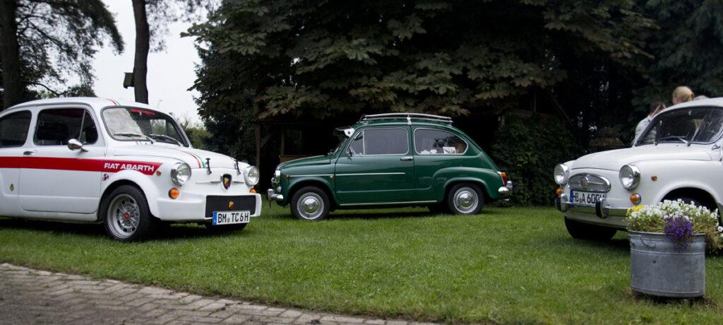 Kreuz und quer stehen die Fiat 600 Freunde im grünen Hof.